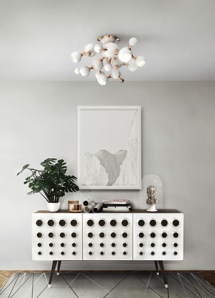 scandinavian hallway white painting wall perforated credenza with pointed and angled legs white picture with white frame grey area rug with modern accent lines unique chandelier