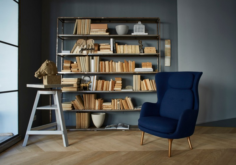 scandinavian home library medium sized book rack bold blue armchair lighter blue walls light wood floors
