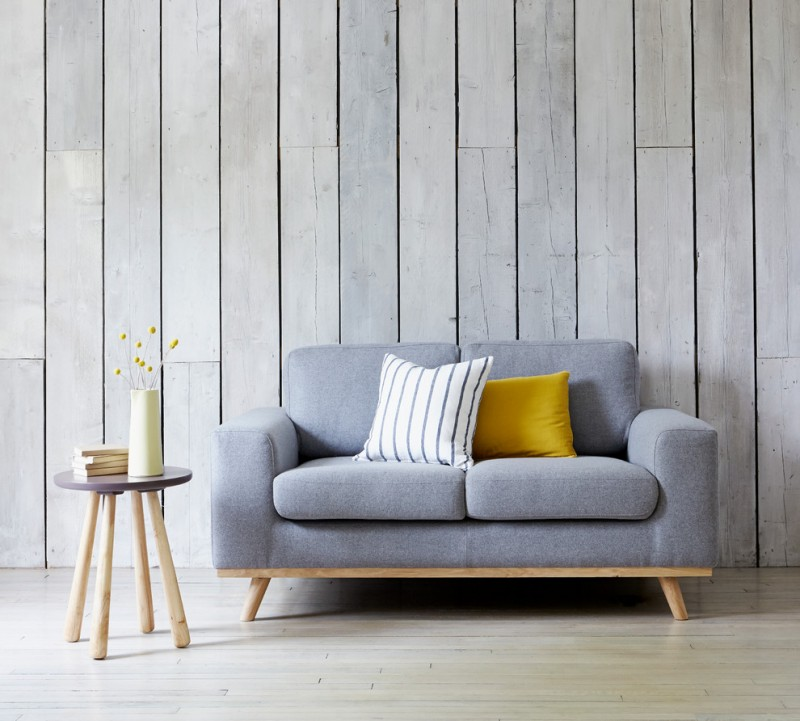 scandinavian living room light grey couch yellow and white stripped throw pillows angled legs side table with round top shabbier vertical wood siding walls white wood floors