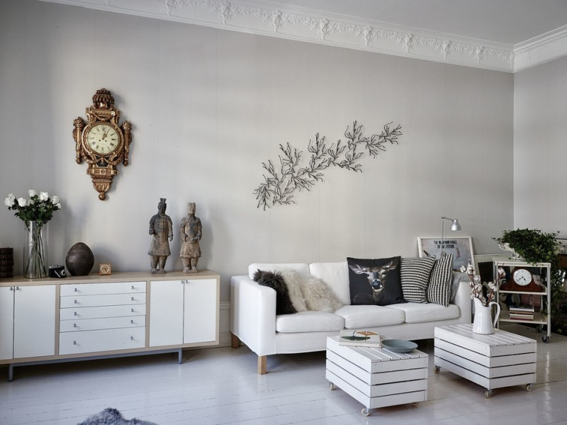 scandinavian living room white couch with throw pillows two wood board center tables with wheels white display cabinet with light wood frame Chinese sculptures antique wall clock in gold
