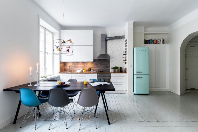 scandinavian open plan kitchen turquoise refrigerator solid black dining table doff black dining chairs turquoise dining chairs white wood siding floors darker wood backsplash white flat paneled cabin