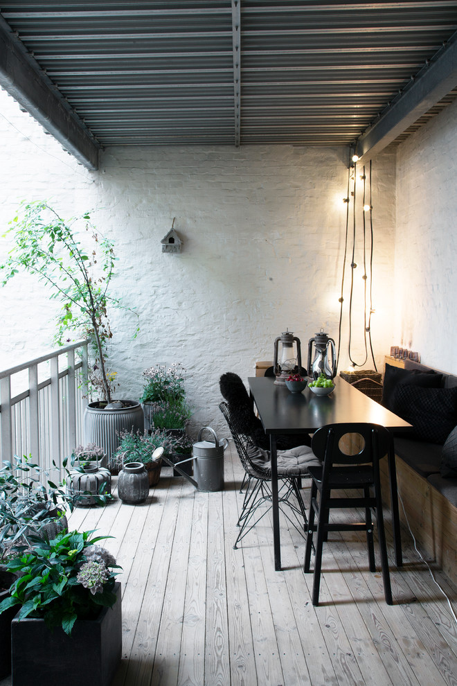 scandinavian outdoor dining space black dining furniture light grey wood board floors textured white concrete walls industrial lighting fixtures