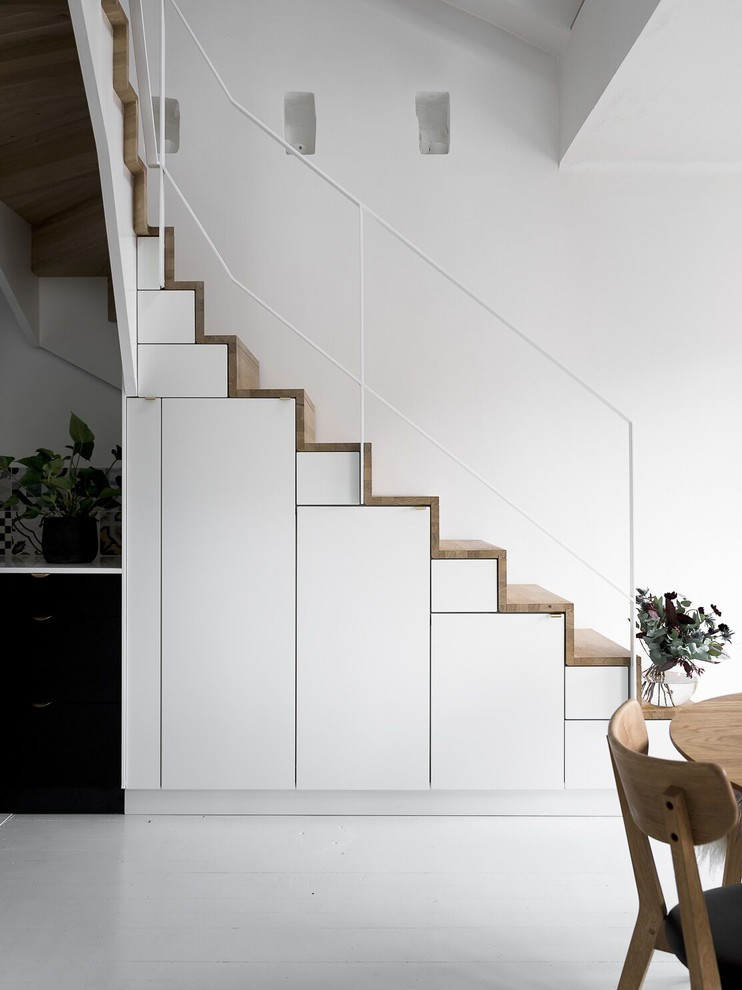 scandinavian staircase with minimalist railings wood steps flat paneled stair storage in white