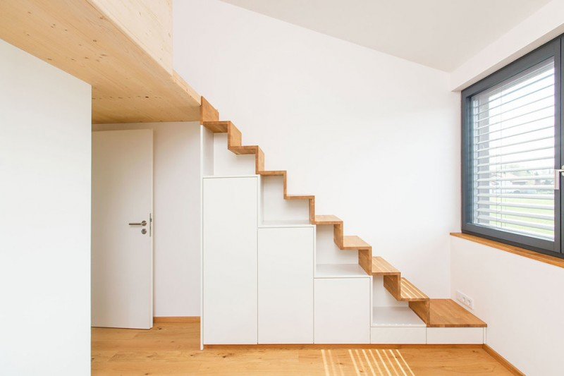 scandinavian staircase without railings white flat paneled stair cabinet and open shelves medium toned wood floors and steps