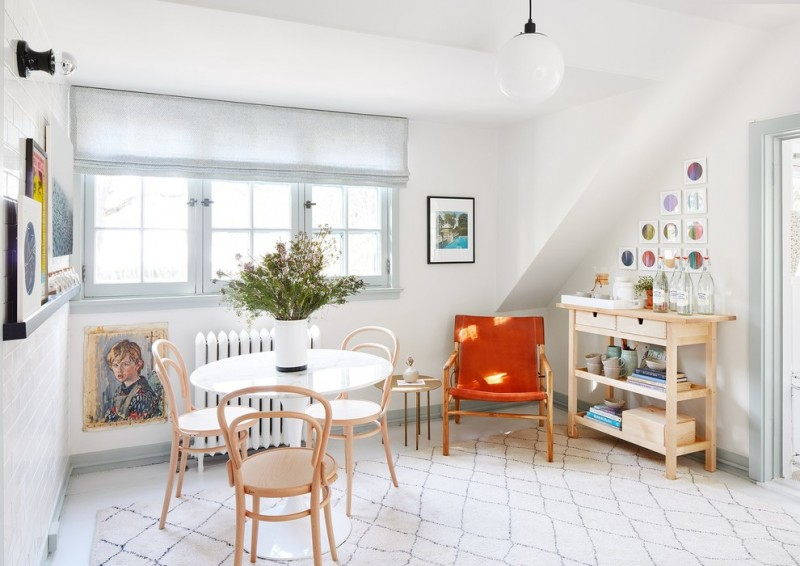 scandinavian style entryway idea light toned wood chairs round top table in white bright orange armchair light wood display cabinet white rug with modern dark patterns white walls
