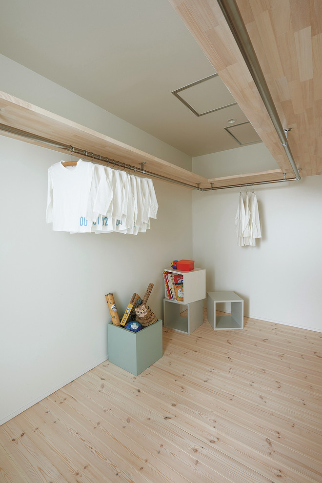 scandinavian walk in closet idea light wood floors white walls stainless steel rails for clothes cubes for seats & storage