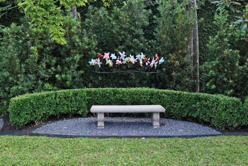 seating corner concrete made bench with curved greens fences colorful stars shaped garden lamps