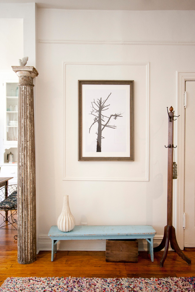 shabby chic hallway lower bench in blue old & unused pillar wood coat hang tree picture on frame dark wood floors multicolored area rug