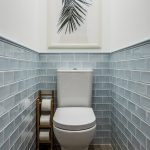 Small Beach Style Bathroom Light Blue Tiled Walls White Painted Concrete Walls White Toilet Wood Tissue Stand Wood Like Tiled Floors