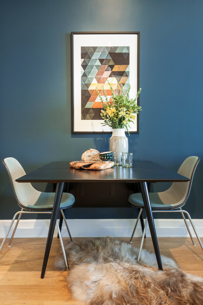 small contemporary dining room bold blue painting wall digital abstract painting art black dining table white midcentury modern dining chairs fury rug medium toned wood floors