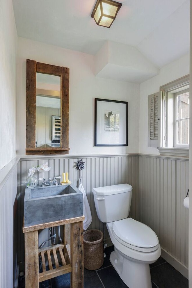small farmhouse bathroom concrete made sink supported by hardwood white toilet vertical siding baseboard wood framed mirror smaller window with shutters