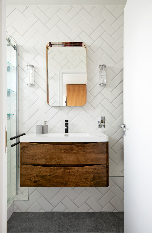small midcentury modern bathroom hardwood bathroom vanity with undermount sink frameless mirror white herringbone tiled walls grey cement floors a pair of modern vanity lamps
