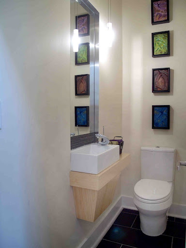 small modern bathroom design vertical art frame wall decors white toilet light wood vanity white farmhouse sink black tiled floors