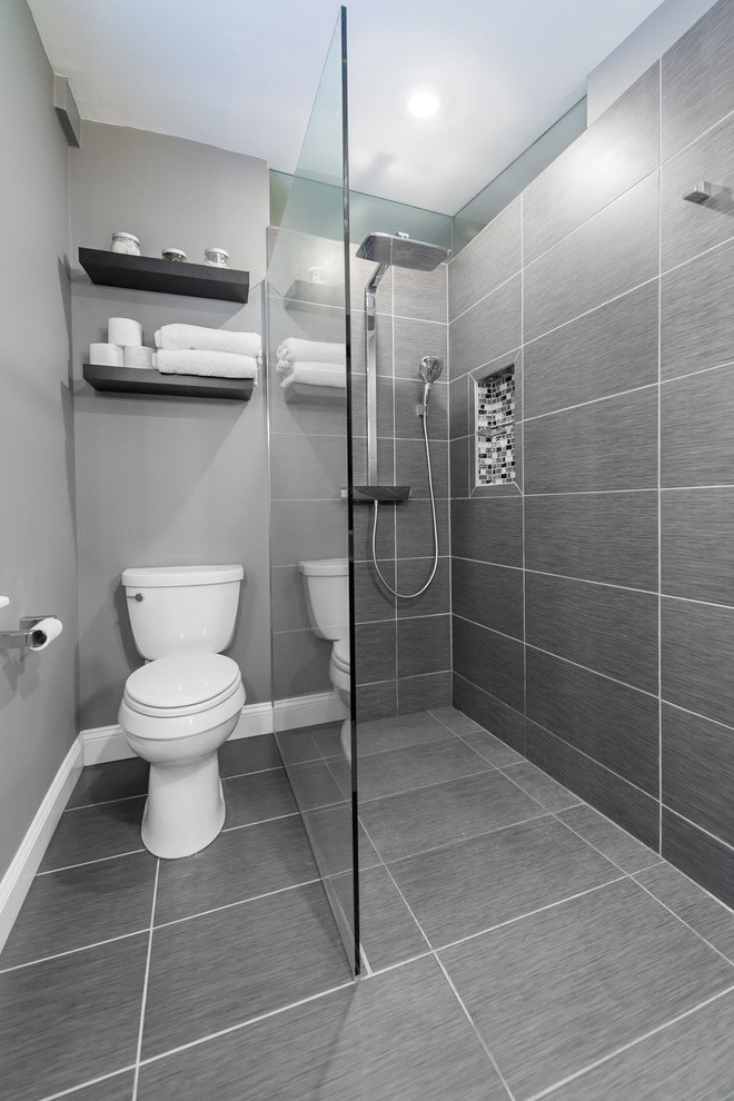 small modern walk in shower with stainless steel shower fixtures glass partition white toilet grey tiled floors grey painted walls