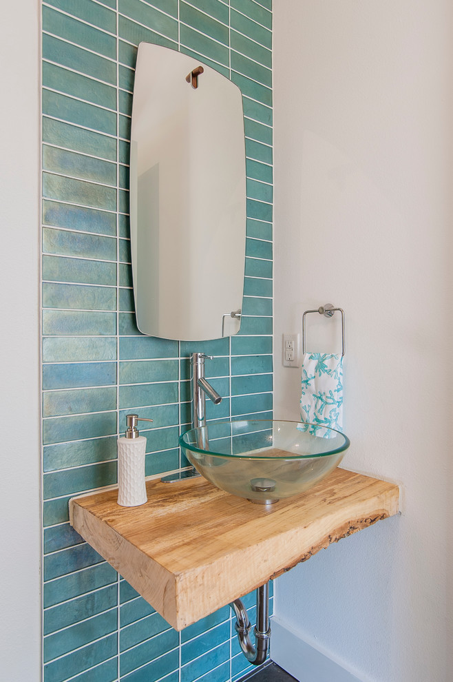 small powder room a piece of wood vanity with glass vessel radiant aquatic blue tiles wall background
