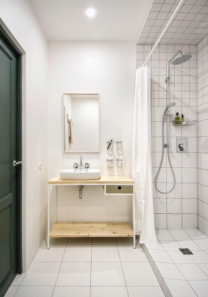 small scandinavian bathroom white painted walls light wood countertop white vessel sink white shower curtain white ceramic tiles floors