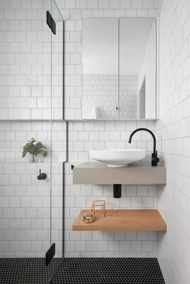 small size scandinavian bathroom white subway tiles wall system glass door with hinges floating vanity with additional floating under wood piece shelf white vessel black mosaic floors frameless mirror