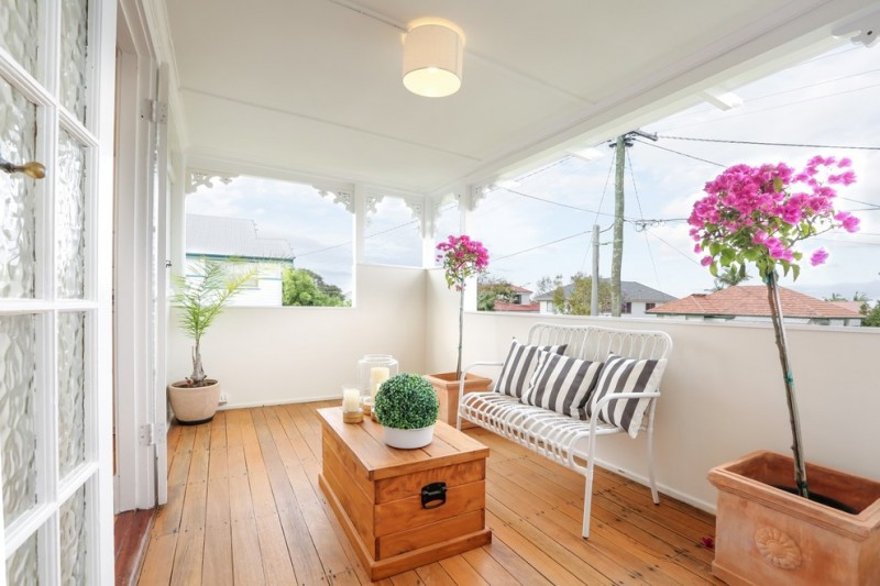 small sized Danish front porch white wall and ceiling medium toned wood floors medium toned wood center table white coated metal sofa stripped throw pillows