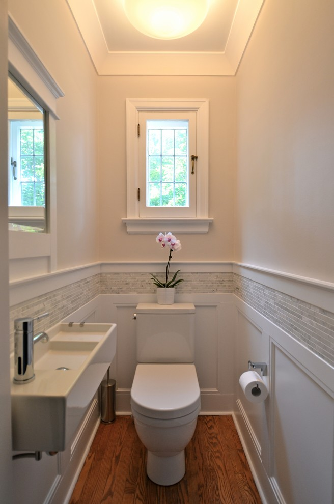 small traditional bathroom white painted walls glass window with white trim white baseboard white bathroom fixtures farmhouse sink in white darker wood floors