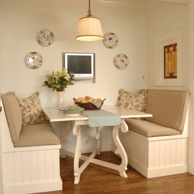 small traditional breakfast nook a pair of banquettes with throw pillows white square top table medium toned wood floors antique decorative plates for walls traditional pendant