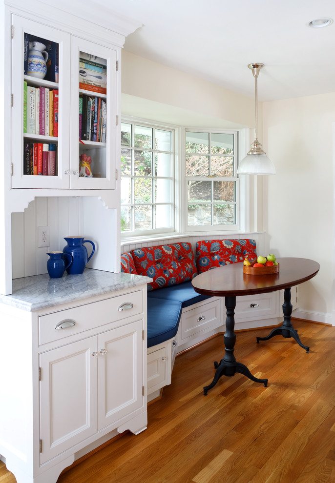 small traditional kitchen nook built in bench seat with red fabrics back dark wood table in oval shape medium toned wood floors white kitchen set