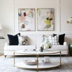 Transitional Living Room Design White Couch Dark Blue Velvet Throw Pillows Flower Motifs Throw Pillows White Round Top Coffee Table With Gold Accent Lines Light Blue Rug Abstract Painting