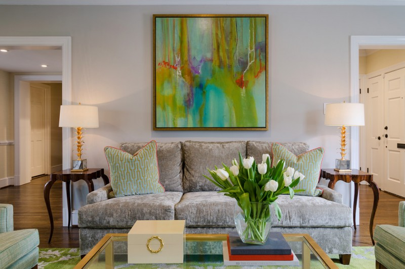 transitional living room green abstract picture with gold frame light grey couch with greenie throw pillows fresh & vivid decorative plants on glass vase glass top coffee table with gold edge lines
