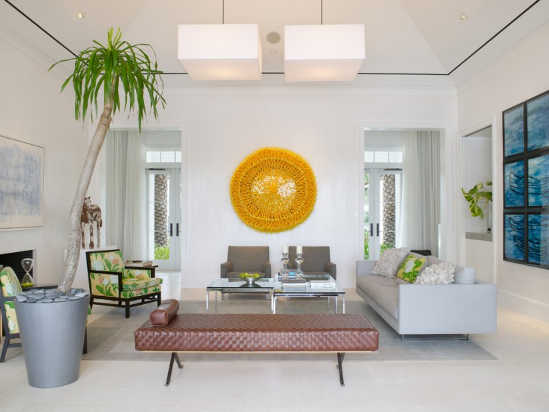 tropical concept living room pop of yellow wall decor medium sized palm tree on planter modern white couch two grey chairs green chairs brown leather seat