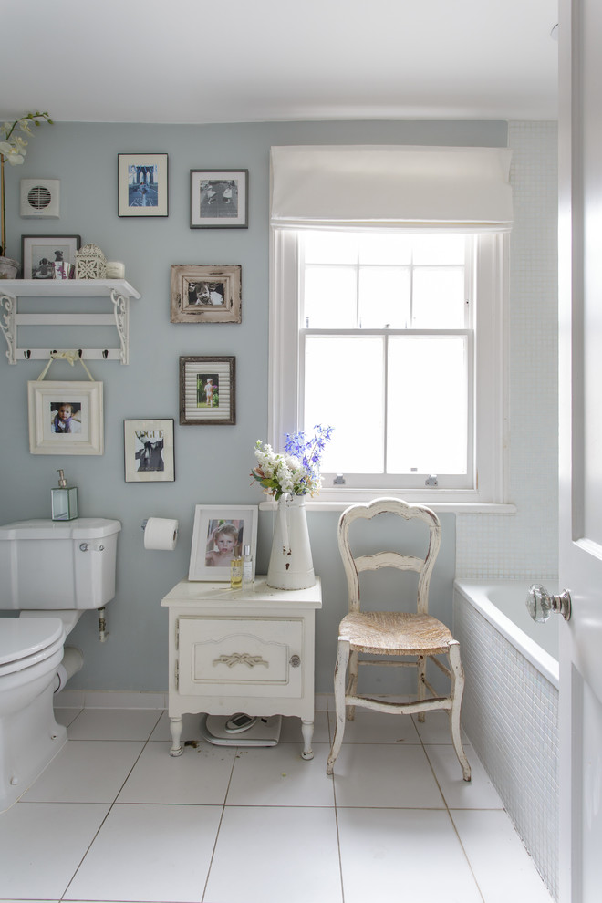 vintage feel chair vintage style side table in white white tiles floors light blue walls with picture frame decorations white toliet window with white shutter