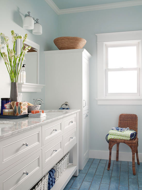 white painted trim white bathroom vanity with marble countertop white cabinets aquatic blue tiles floors very light blue wall painting wood woven chair