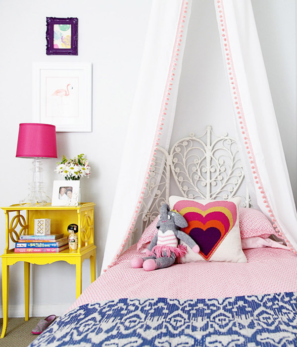 Bohemian style bed frame with white metal headboard accented with handcraft details bright yellow bedside table table lamp with magenta lampshade