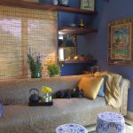 China styled family room blue painted walls woven wood window blind Chinese porcelain ware Chinese styled tables bamboo floors gold toned couch