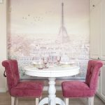 French style dining room Eiffel Tower graphic background wall accented by light pink ornate flowers white round top dining table French style chairs in pink
