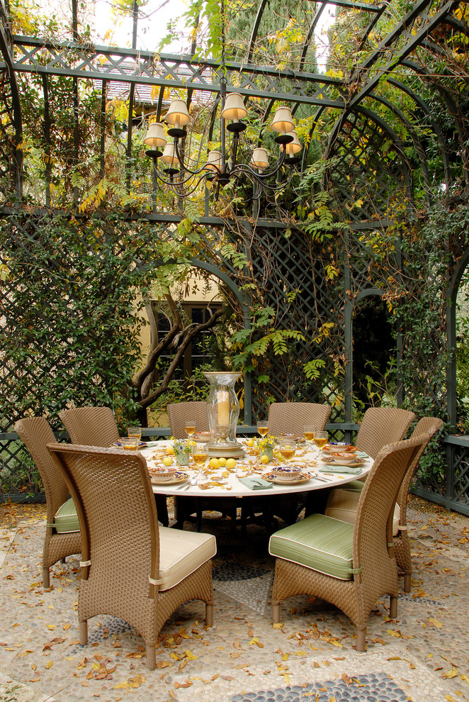 Tuscan style patio built from iron lattice and canopy traditional chandelier woven outdoor seats with green seaters large round top outdoor table