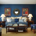 Apartment Sized Living Room Navy Blue Painted Walls Traditional Chinese Artworks Blue Sofa Dark Wood Coffee Table Brown Area Rug A Couple Of White Table Lamps Wooden Side Tables