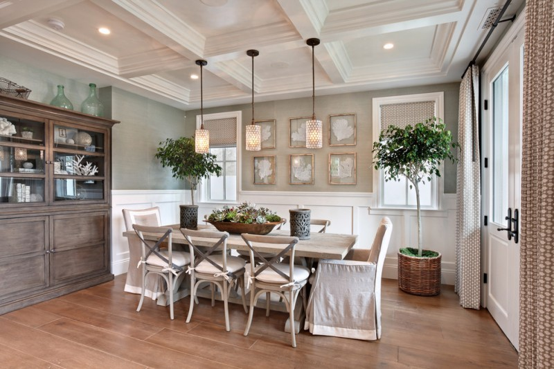 beach style dining room traditional style dining chairs side chair slipcovers light wood dining table medium toned wood floors warm lighted pendants light grey painted walls