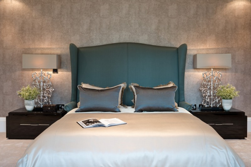 bed frame with classic style headboard in blue dark wood bedside tables statement bedside lamps with warming lighting