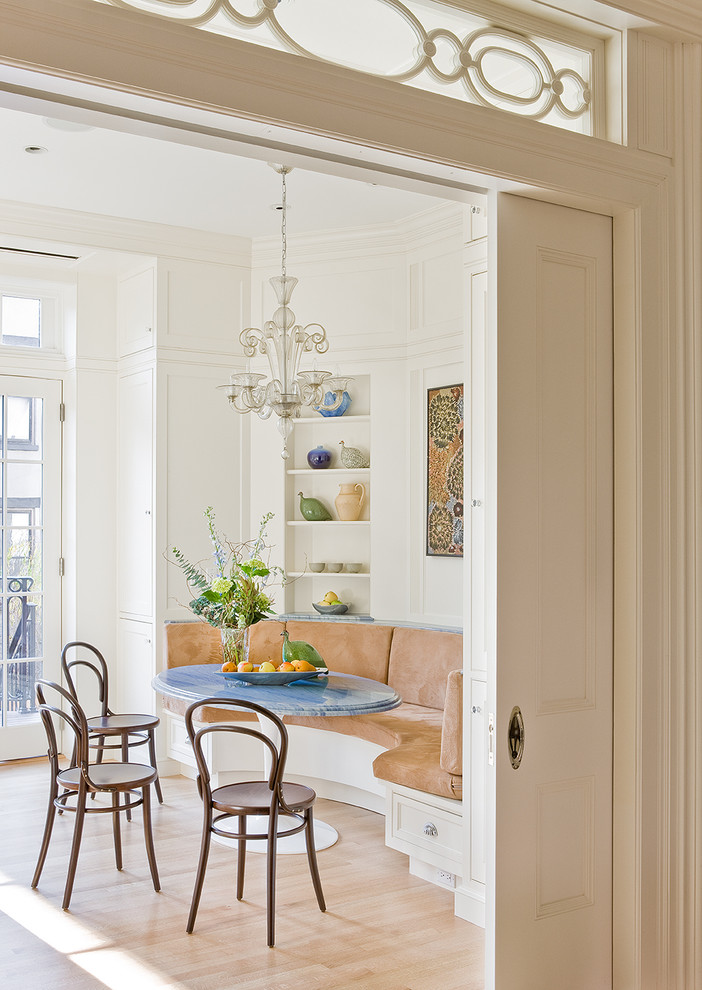 breakfast nook nearest the transom windows corner built in bench with light brown foam blue round top table dark finished bamboo chairs light toned brown floors white painted walls recessed shelving u