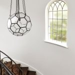 clean lines stair area large transparent crystal pendant with chain holders mediterranean style glass window dark wood staircases and black wrought iron railings
