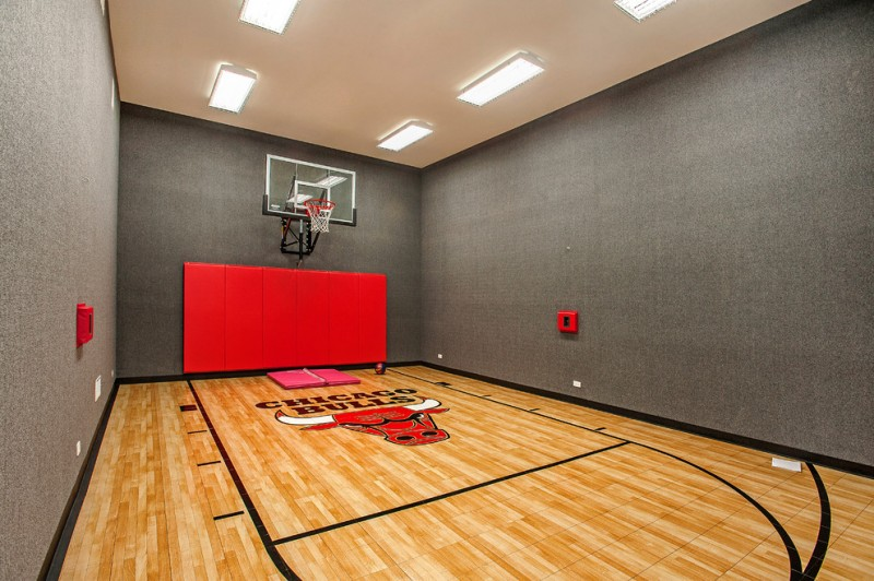 contemporary indoor basketball court design gloss maple floorings grey carpeted walls cream painted ceilings red backboard