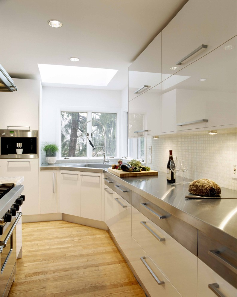 contemporary kitchen design stainless steel corner sink stainless steel countertop light wood floors white cabinets with silver handles stainless steel appliances