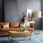 contemporary living room idea worn out light brown leather sectional white covered throw pillows industrial storage coffee table blackwashed walls