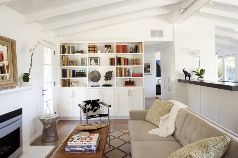 contemporary living room white painted walls white painted shelving modern fireplace light beige couch cowhide armchair medium toned wood floors butcher block coffee table