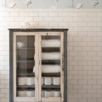 eclectic cabinet with clear glass panel and white shabby frames white subway tiles walls grout wood floors