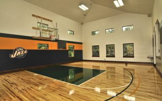 large indoor basketball court design with high gloss wood laminated floors orange black painted walls