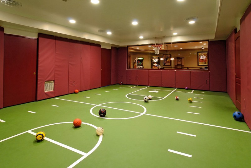 large indoor basketball court with green floors and maroon wall panels
