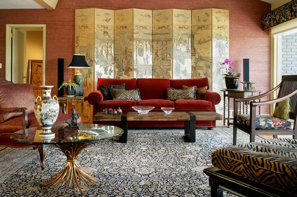 large living room red sofa round glass top coffee table Chinese screen in gold multicolored area rug red brick toned walls
