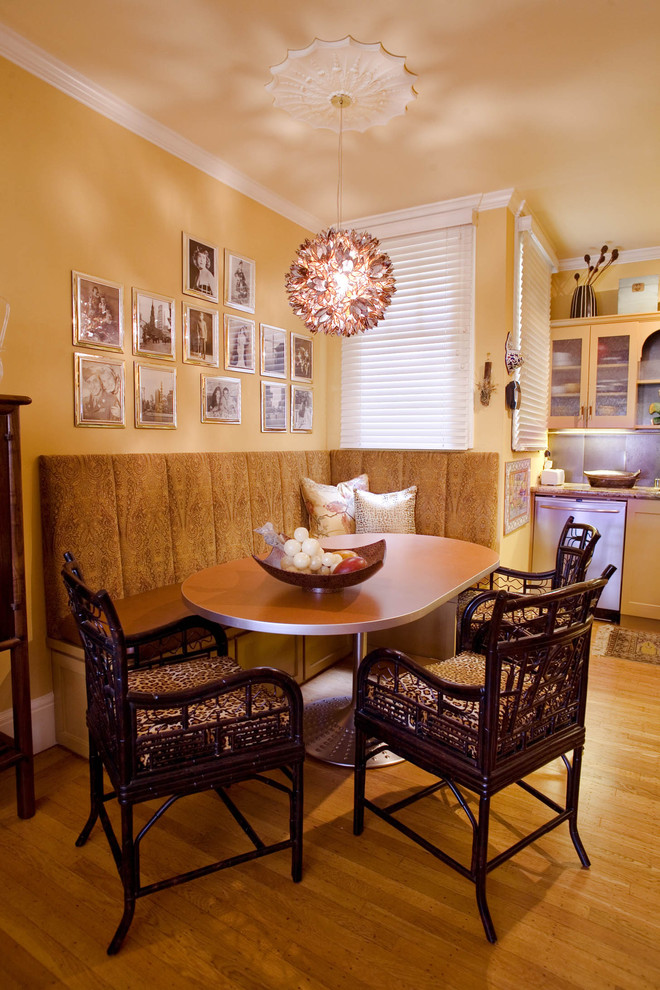 low lighted and warm breakfast nook corner built in banquette with higher back semi circular wood table dark finishing chairs deep cream painted walls series of picture frames