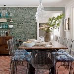 mediterranean dining room red brick floors multicolored mosaic tile walls three glass pendants farm dining table wire dining chairs with fabric seater