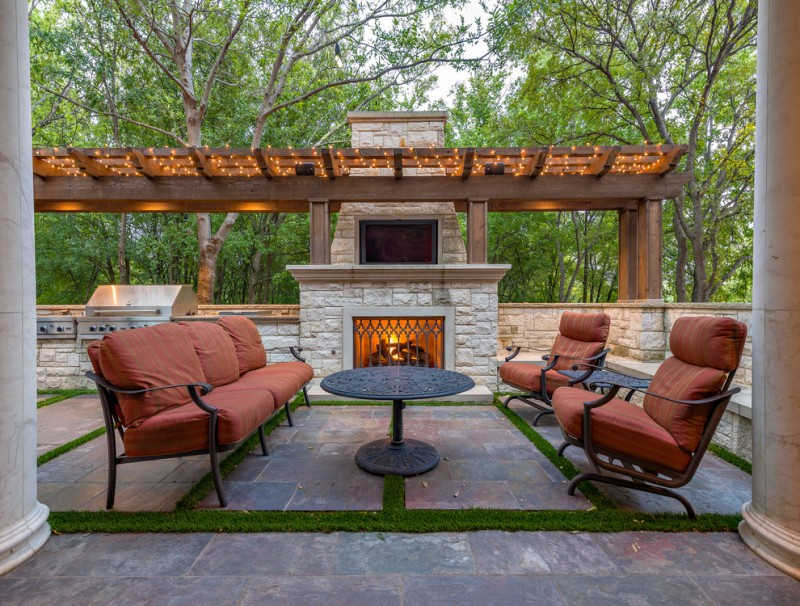 mediterranean patio design with pergola string lamps outdoor fire pit black wrought iron table with round top black wrought iron seats with red seaters terracotta tiles floors